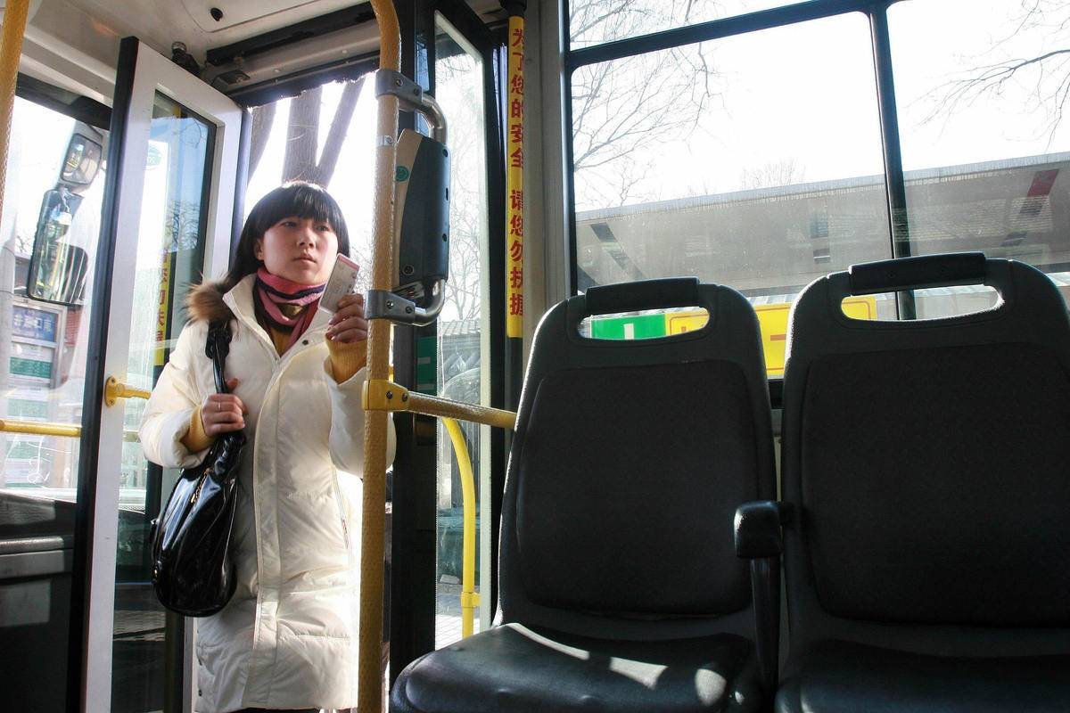 A Chinese woman boards a public bus in B